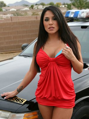 Latina milf is taking off top lingerie posing outdoor near police car