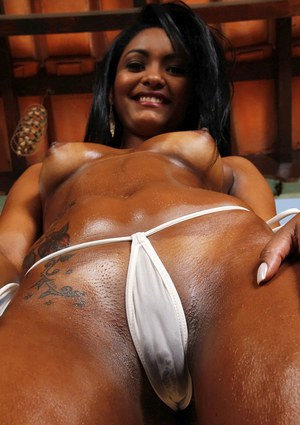 Mouth watering Latina chick with oiled body teases her dark pussy near a pool