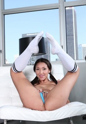 Latina solo girl Vicki Chase models in a chair wearing knee high socks